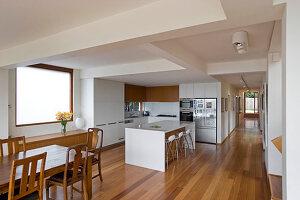 Offene Küche mit Kücheninsel, im Vordergrund Esstisch aus Holz mit Stühlen