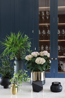 Hydrangea, thistles and twigs in black and golden vases