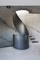 Concrete winding staircase with curving metal balustrade
