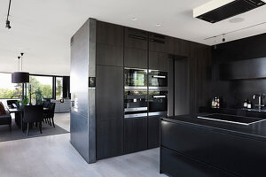 Black, modern kitchen in open-plan interior in shades of grey