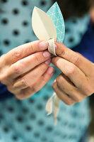 Selbstgebastelte Papieranhänger in Blattform mit Band als Dekoration