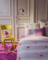 Feminine bedroom with pink carpet, yellow chair and standard lamp