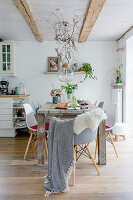 Wooden table, classic chairs and summery arrangement of plants in Scandinavian-style dining room
