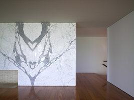 Marmorwand mit Kamin in minimalistischem Wohnraum