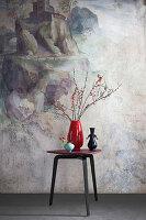 Drei Vasen auf Designertisch vor Wandmalerei