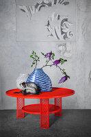 Weiße Glasvase, blaue Keramikvase mit Fischdekor und Porzellanaffe auf rotem Stahlgittertisch
