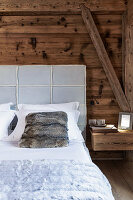 Bed with upholstered headboard and fur scatter cushion against rustic wooden wall