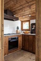 Moderne Einbauküche mit rustikalen Holzfronten und Dachschräge