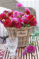 Strauß aus roten und pinken Dahlien im Korb