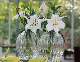 Weiße Lilienblüten in Glasvasen