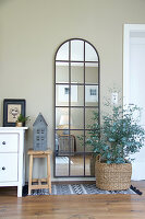 Arched, lattice mirror on wall and eucalyptus planted in basket in living room