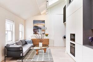 Polstersofa und Coffeetable vor Einbauküche in hellem, offenem Wohnbereich