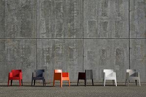 Farbige Kunststoffstühle auf der Straße vor Beton-Fassade