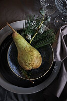 Place setting festively decorated with pear and sprigs of eucalyptus and pine