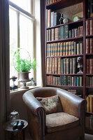 Vintage Ledersessel vor Bücherregal und Fenster in Zimmerecke