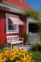 Bench below window with awning outside Falu-red Swedish house during summer