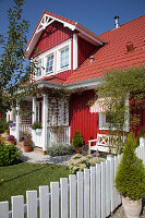 Falu-red Swedish house with porch, dormer window and sunny front garden