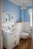 White wooden wainscoting and blue walls in small bathroom