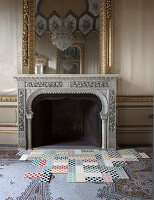 Moderne Fliesen mit geometrischen Mustern auf antikem Mosaikfliesenboden vor Kamin
