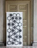 Moderne Fliesen mit grau-weißen Mustern auf Platte vor antiker Tür