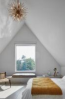 Schlichtes Schlafzimmer unter der Schräge mit Sitzbank vorm Fenster