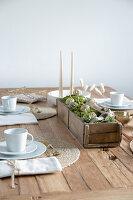Selbstgemachte Tischdeko mit Schnecken aus Steinen und Draht