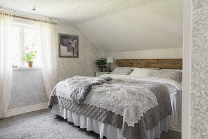 Pretty bedroom with patterned wallpaper and crocheted blanket on double bed