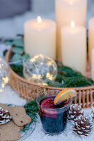Mulled wine and spiced biscuits next to tray of candles and illuminated spheres