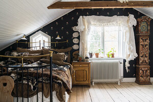 Metal bed and floral wallpaper in bedroom below sloping ceiling
