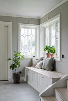 Chest bench below window in hallway with pale grey walls