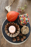Autumnal arrangement of origami candle holder, pumpkin and envelope