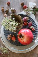Herbstliche Tischdeko mit Granatapfel, Mohnkapseln und Hortensienblüten