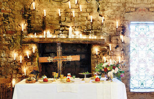 Festively set table in front of old wall decorated with cross and candles