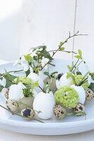 Österliches Arrangement aus Eiern und Frühlingsblumen