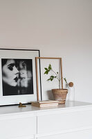 Framed portrait of woman next to potted plant on white chest of drawers