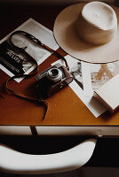 Vintage camera, sun hat and pictures on table