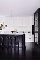 Offene Küche mit weißen Schränken, Kücheninsel und dunklem Dielenboden