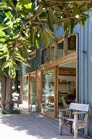 Wohnhausfassade mit Holrahmenfenstern und blauer Metallverkleidung