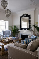 Beige sofa and blue armchair in seating area in front of fireplace