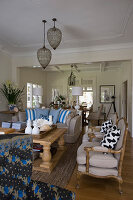 Sofa, solid wooden table and antique armchairs in living room