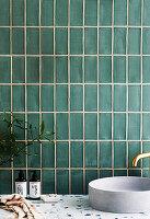 Waschtisch mit Handwaschbecken vor grüner Fliesenwand