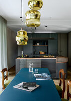 Metal dining table with blue top in front of modern kitchen in shades of grey