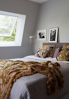 Double bed in bedroom with grey, slightly sloping walls