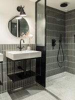 Shower area in bathroom with grey tiles