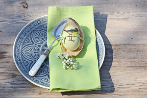 Easter egg with bird motif and green napkin on blue plate