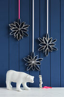 Snowflakes handmade from toilet roll tubes against blue board wall