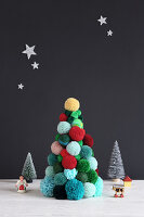Christmas tree made from colourful pompoms against black wall