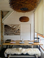 Sheepskin rug on bench at set dining table below pendant lamp made from branches
