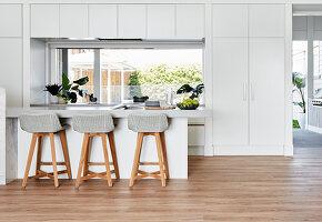Minimalistische weiße Küche mit Einbauschränken und Theke