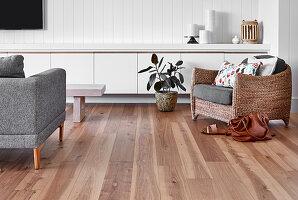 Korbsessel und weißes Sideboard im Wohnzimmer in Naturtönen